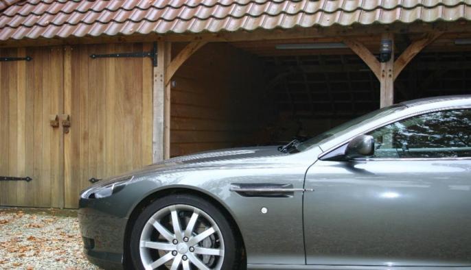 eiken bijgebouw met carport en houten garage voor aston martin